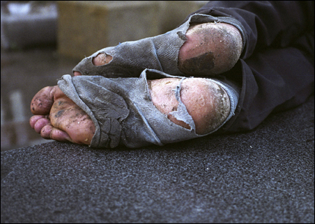 The feet of a homeless man are seen as he naps on a street of Shenzhen